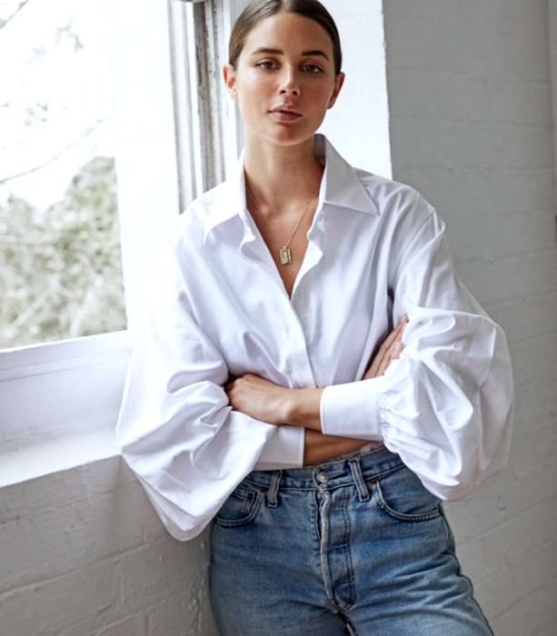 brown haired girl wearing white oversized shirt with puff sleeves, waist mom jeans