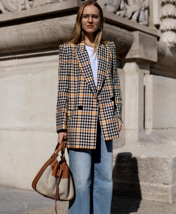 blonde girl wearing glasses, white t-shirt, yellow oversized blazer with black plaid, baggy jeans and beige and brown leather bag