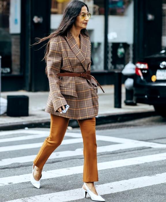 chica de cabello castaño largo usando un blazer oversized café de cuadros, cinturón café, pantalones cafés de vestir y zapatos blancos de tacón