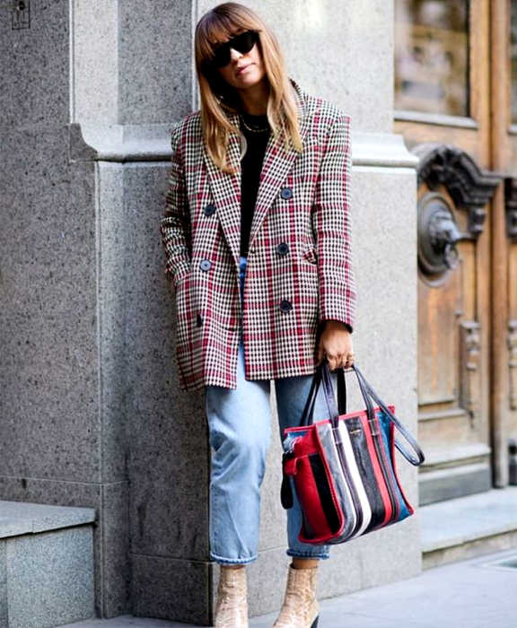 blonde haired girl wearing sunglasses, black top, gray red plaid blazer, waist mom jeans, beige leather ankle boots, red, white, blue and black handbag