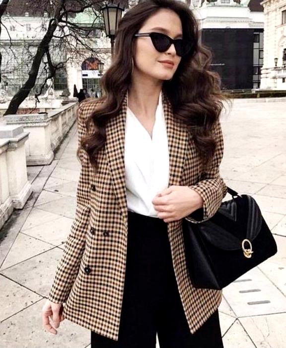 chica de cabello castaño usando lentes de sol, blusa blanca, pantalón negro de vestir, bolso negro de mano