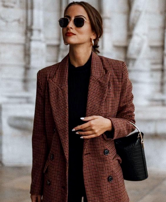 Brown haired girl wearing sunglasses, black top, brown checked blazer and black jeans, black leather bucket bag