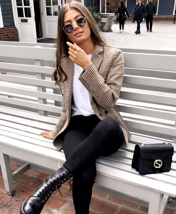 girl with light brown hair wearing sunglasses, white t-shirt, beige brown checked blazer, black skinny jeans, black leather ankle boots and black mini bag