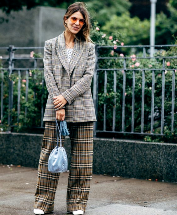 Light-haired girl wearing sunglasses, white top with polka dots, gray plaid blazer, brown plaid dress pants, white ankle boots, light blue bucketbag