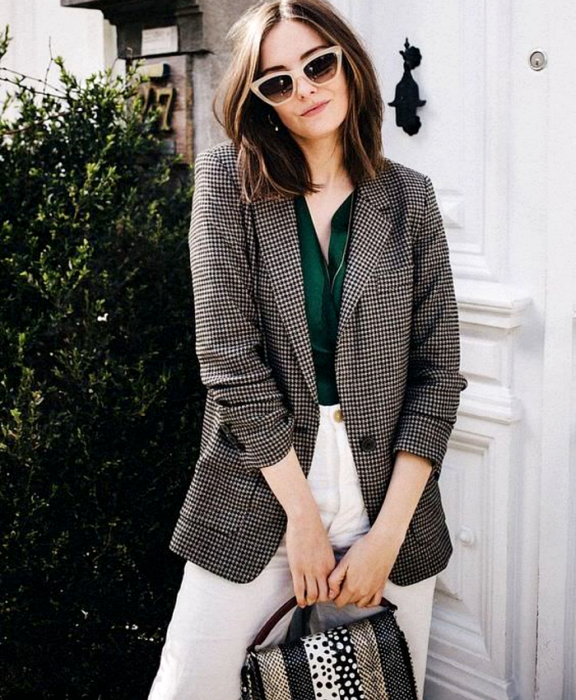 girl with light brown hair wearing beige sunglasses, emerald green blouse, brown and gray plaid blazer, white pants, white, gray and beige patterned handbag