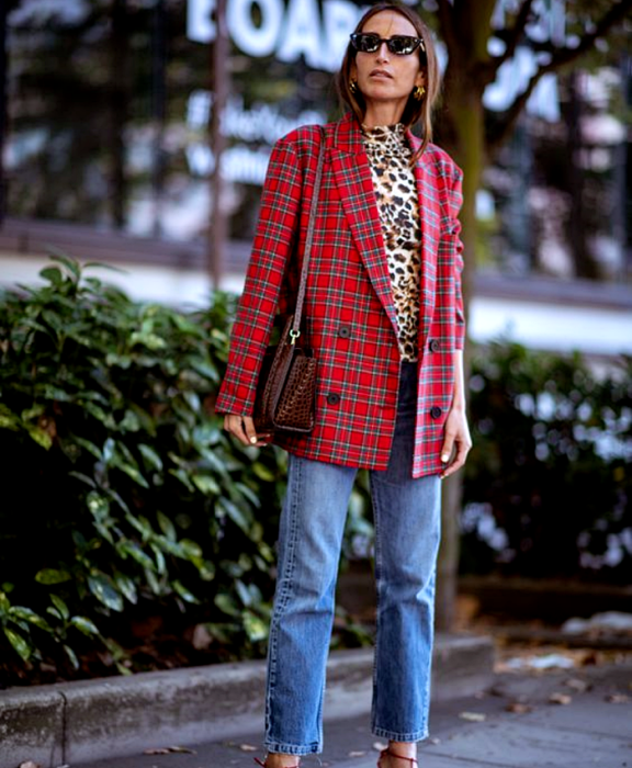 light haired girl wearing sunglasses, animal print top, red plaid blazer, straight jeans, brown leather bag