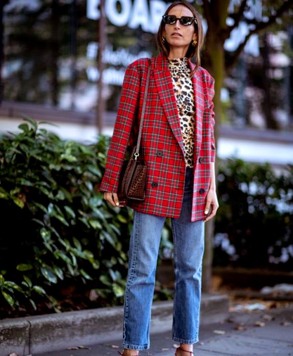 chica de cabello claro usando lentes de sol, top estampado de animal print, blazer rojo de cuadros, jeans rectos, bolso café de cuero