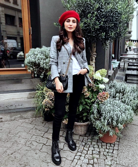 chica de cabello castaño usando un beret rojo, blazer gris de cuadros, top blanco, skinny jeans negros y botines negros de piso, bolso negro de cuero