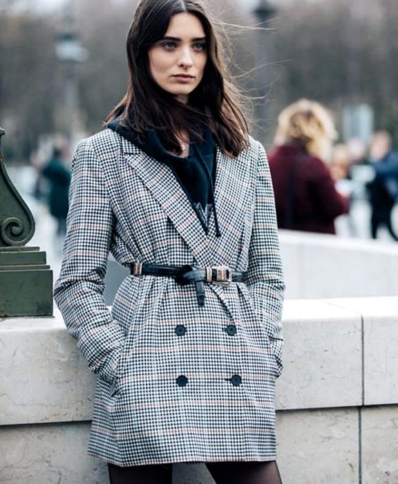 chica de cabello oscuro usando una sudadera negra, blazer gris de cuadros, cinturón negro de piel, medias semi-transparentes