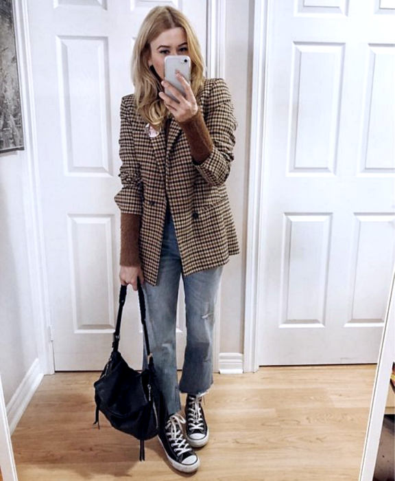 blonde girl wearing brown plaid blazer, brown sweater underneath, straight jeans, black converse and black leather bag