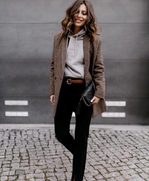 chica de cabello castaño usando una sudadera gris, blazer café de cuadros, cinturón café, pantalones de vestir negros, bolso de mano negro