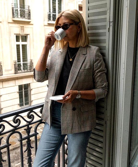 blonde girl wearing sunglasses, black top, brown plaid blazer, waist jeans drinking coffee