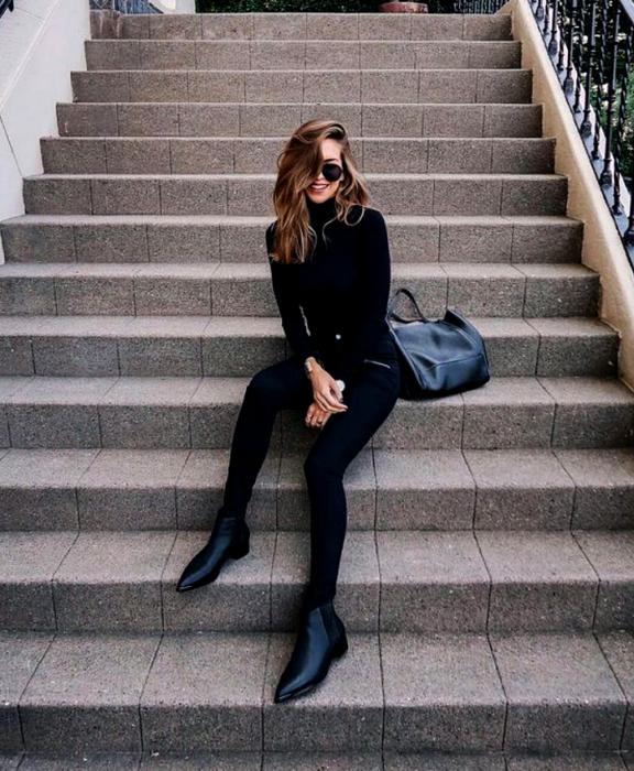 chica de cabello claro usando lentes de sol, top de manga larga y cuello alto negro, leggings negros y botines de cuero sin tacón, bolso de mano  negro