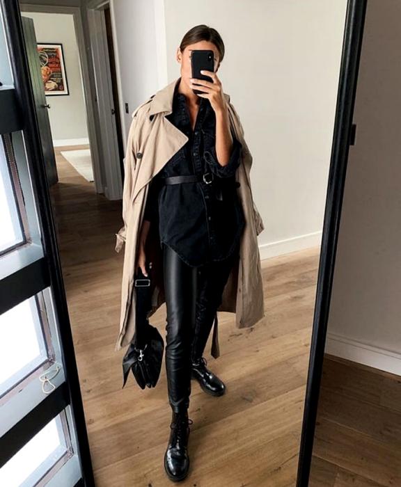 chica de cabello castaño usando un abrigo largo café, camisa de botones negra, cinturón negro, leggings de cuero negro, botines de piso negro y bolso de mano negro