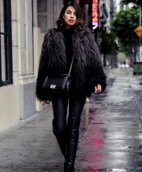 chica de cabello castaño usando un abrigo furry morado con negro, leggings negros de cuero, botas largas de cuero, bolso negro y top negro