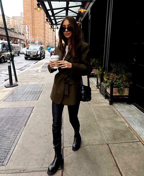 chica de cabello castaño usando lentes de sol, top blanco, abrigo verde militar, leggings negros de cuero, botines negros de piso y bolso mini negro puffer