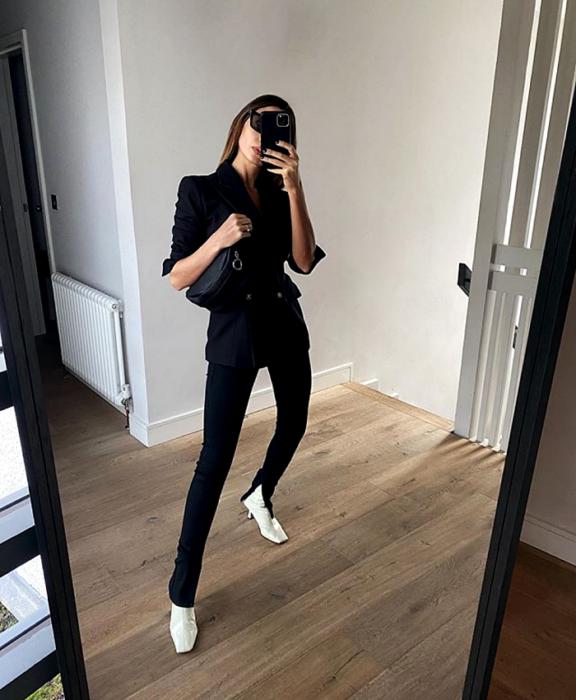 chica de cabello castaño usando lentes de sol, blazer azul marino, leggings negros con apertura en el tobillo, botines blancos de tacón y bolso mini de mano negro