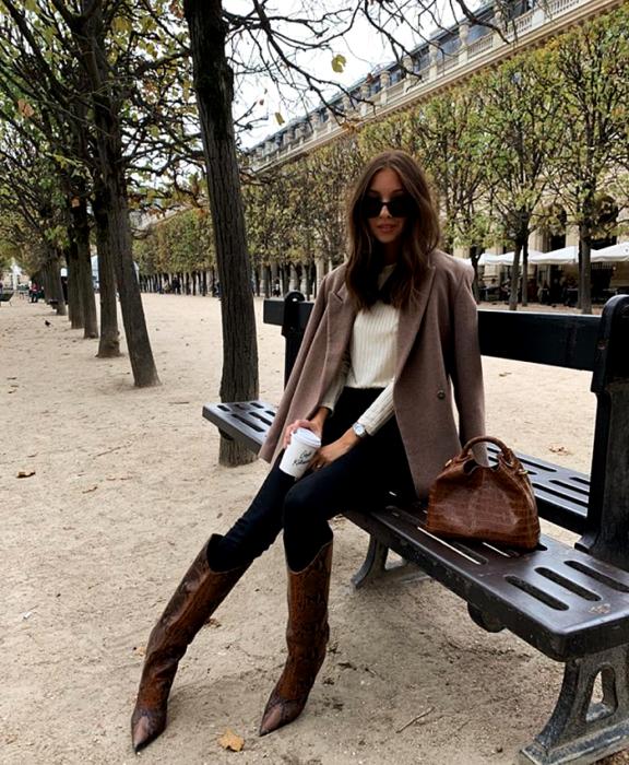 chica de cabello castaño usando lentes de sol, suéter blanco, abrigo café, leggings negros, botines cafés de piel con tacón, bolso de mano café