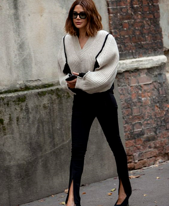 chica de cabello castaño usando lentes de sol, suéter beige de mangas largas y holgadas, leggings negros con apertura en el tobillo y tacones negros