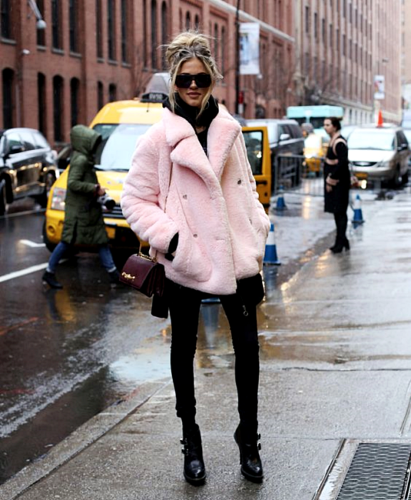 chica rubia usa lentes de sol, abrigo furry rosa, top negro, leggings negros, botines negros de tacón y bolso mini de cuero guinda