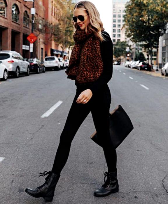 chica rubia usando lentes de sol, bufanda café de animal print, suéter negro de manga larga, leggings negros y botines negros sin tacón y bolso de mano  negro