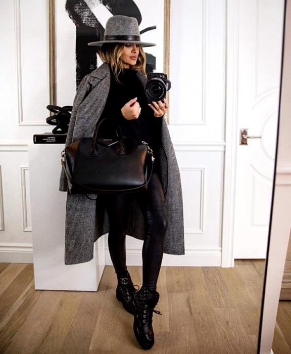 chica rubia usando un sombrero gris con cinta negra, suéter negro, abrigo largo gris, leggings de cuero negro, botines negros sin tacón y bolso grande shopper negro