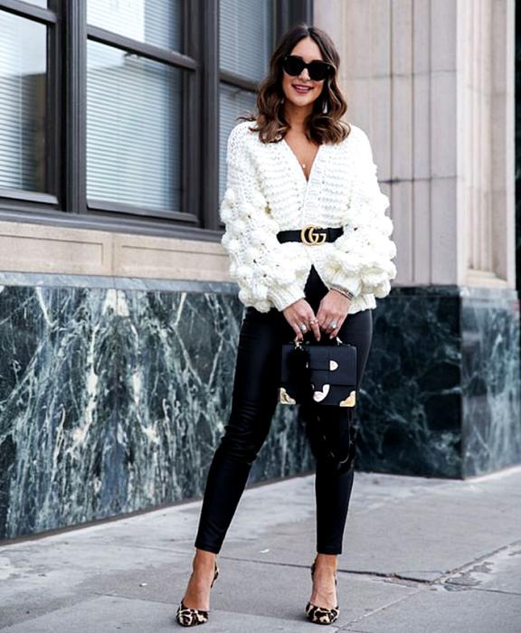 chica de cabello café con lentes de sol, suéter blanco, cinturón negro, leggings de cuero negro, bolso mini de cuero negro, zapatos de tacón con animal print