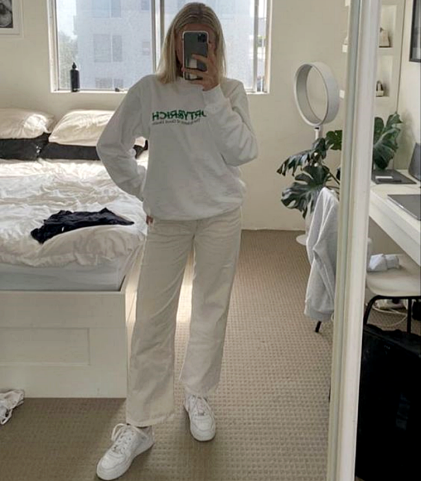 blonde girl wearing a white sweatshirt, white baggy pants and white sports sneakers