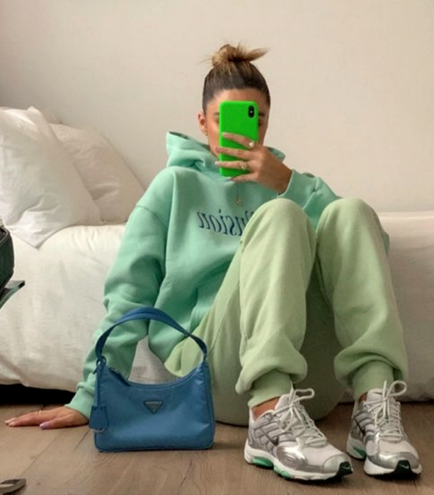 light-haired girl wearing a pistachio green oversized sweatshirt, pastel green pants, gray and white tennis shoes, and blue tote bag
