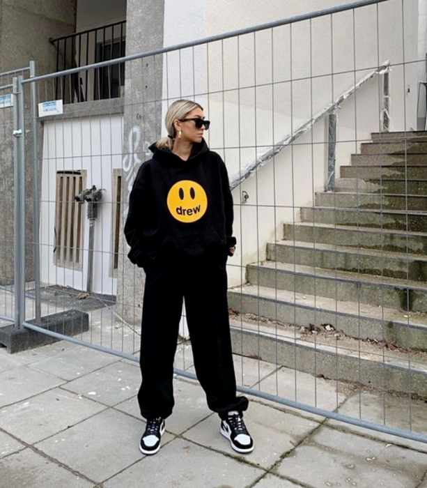 blonde girl wearing sunglasses, oversized black sweatshirt with a happy face, baggy black pants and white sneakers with black
