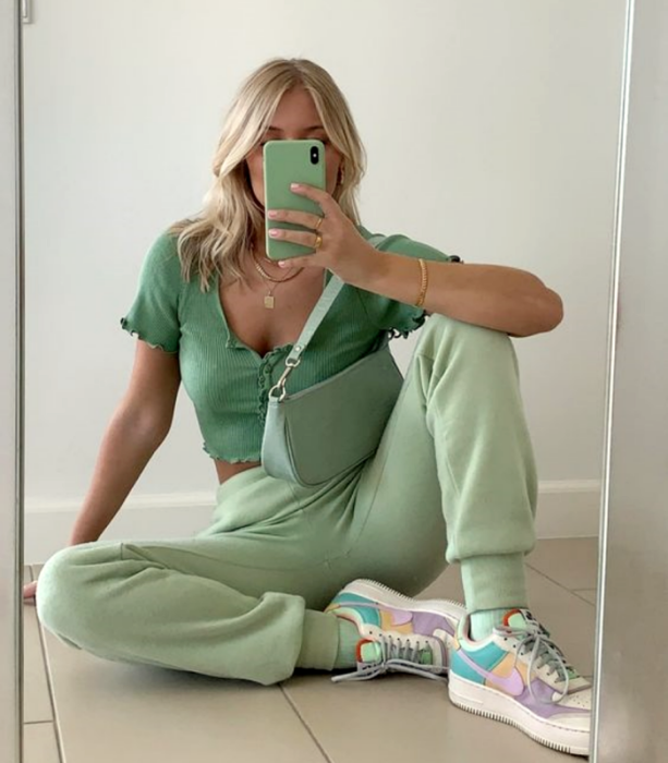 blonde girl wearing green top with buttons, scoop neckline, pistachio green pants and pastel colored nike tennis shoes, pastel green clutch bag
