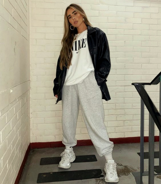 girl with long light hair wearing oversized white t-shirt, leather jacket, gray pants and white sports sneakers