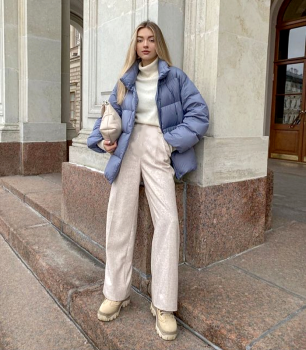 blonde girl wearing white turtleneck sweater, baggy beige pants, sky blue puffer jacket, beige clutch bag, and beige chunky-soled boots