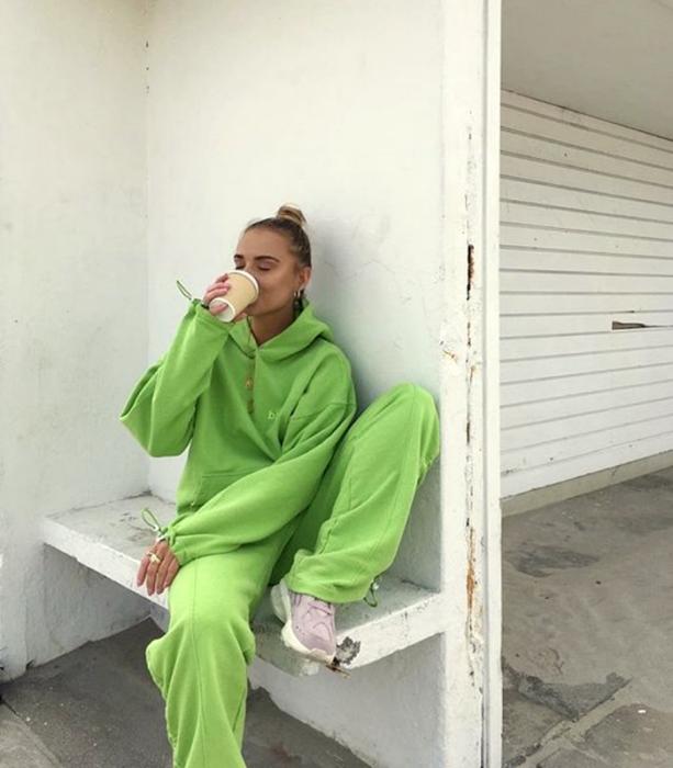 chica rubia usando una sudadera verde neón, pants verde neón y tenis deportivos lila