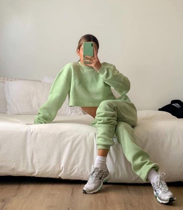 light haired girl wearing pastel green sweatshirt, pastel green pants, white tennis shoes