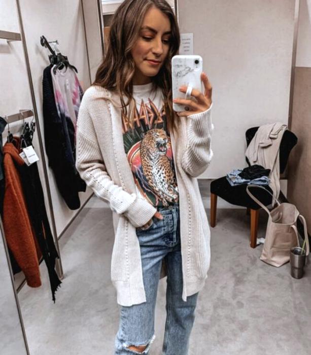 chica de cabello castaño usando una camiseta blanca gráfica estampada, cárdigan beige largo, jeans a la cintura rasgados