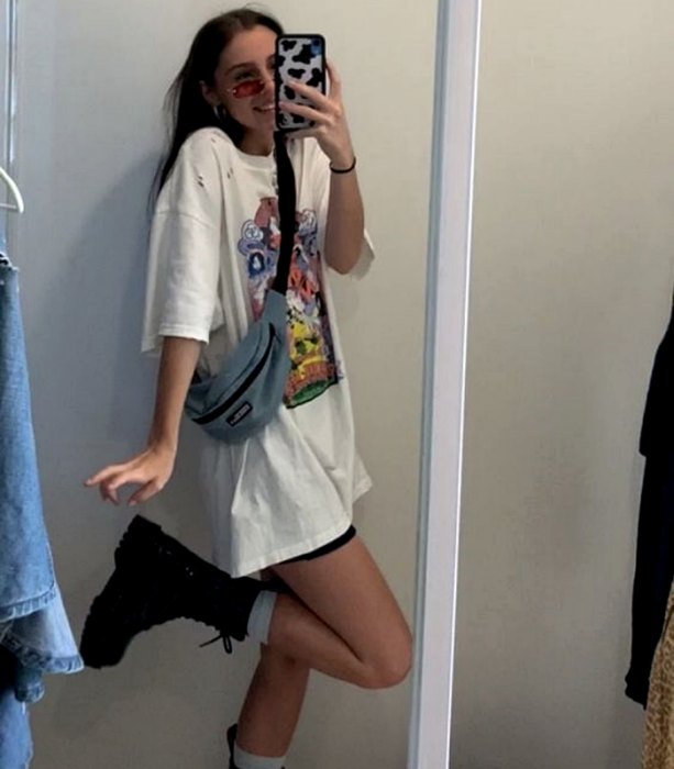 brown haired girl wearing sunglasses, a blue fanny pack, white oversized printed graphic white t-shirt, black cycling shorts, thick-soled leather ankle boots