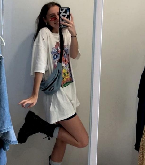 chica de cabello castaño usando lentes de sol, una cangurera azul, camiseta blanca gráfica estampada oversized blanca, shorts negros de ciclismo, botines de cuero de suela gruesa