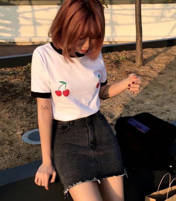 chica pelirroja usando una camiseta blanca estampada gráfica, minifalda negra de mezclilla y bolso de mano negro