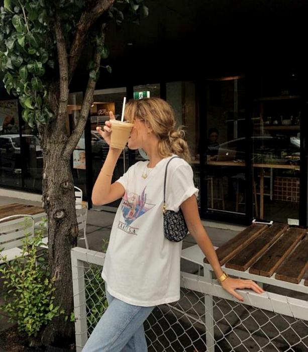 chica rubia usando lentes, camiseta blanca estampada, jeans holgados y bolso de mano  negro con blanco