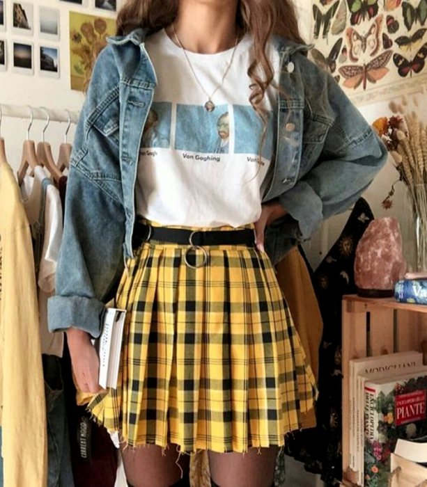 light-haired girl wearing a white graphic print T-shirt, black belt, yellow miniskirt with black plaid, black tights and denim jacket