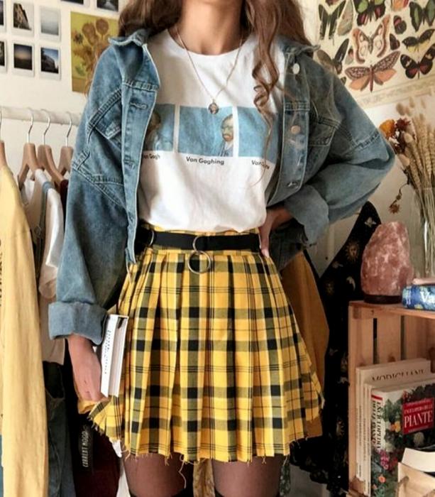 chica de cabello claro usando una camiseta blanca gráfica estampada, cinturón negro, minifalda amarilla con cuadros negros, medias negras y chaqueta de mezclilla