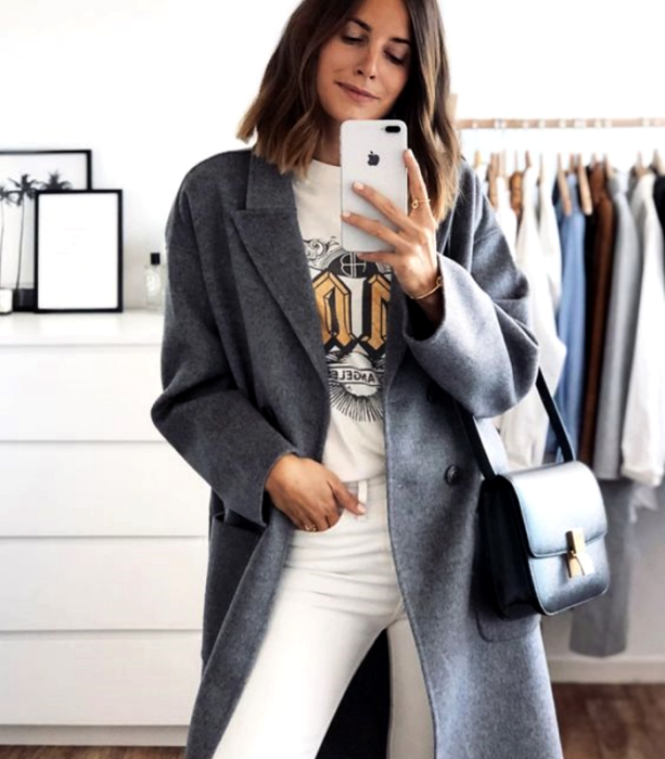brown haired girl wearing graphic print white t-shirt, long gray coat, white denim pants and black leather tote bag
