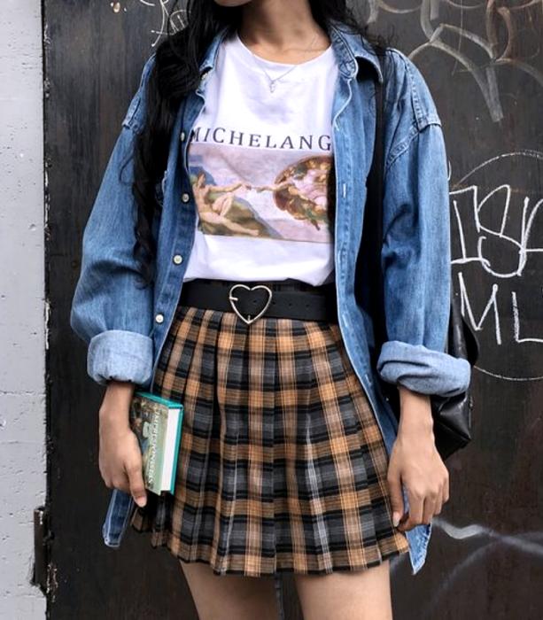 chica de cabello castaño usando una camiseta blanca gráfica estampada, camisa de mezclilla de botones, cinturón negro con hebilla de corazón, minifalda de cuadros naranja con azul