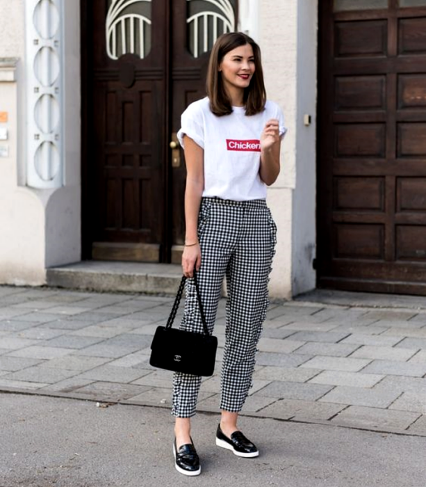 brown haired girl wearing white graphic print T-shirt, black plaid white dress pants, white soled black skirts, and black tote bag