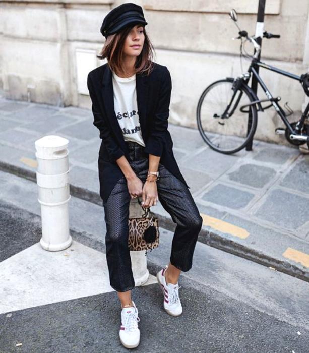 chica de cabello castaño usando un beret negro, camiseta blanca estampada, blazer negro, pantalones de vestir de cuero, tenis deportivos blancos y bolso de mano de animal print