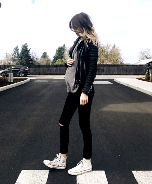pregnant girl with dark hair and hightlights, wearing gray top, black leather jacket, black skinny jeans, white converse sneakers