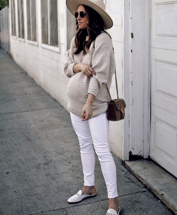 pregnant long hair girl wearing sunglasses, beige large brim hat, beige oversized sweater, white skinny jeans, white loafers shoes, crossover coffee bag