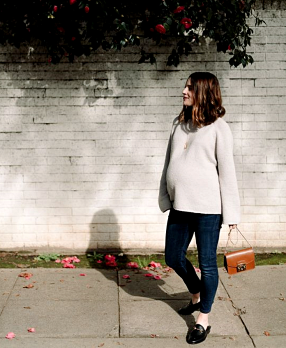 brown haired, pregnant girl wearing gray oversized sweater, skinny jeans, black loafers, orange clutch bag
