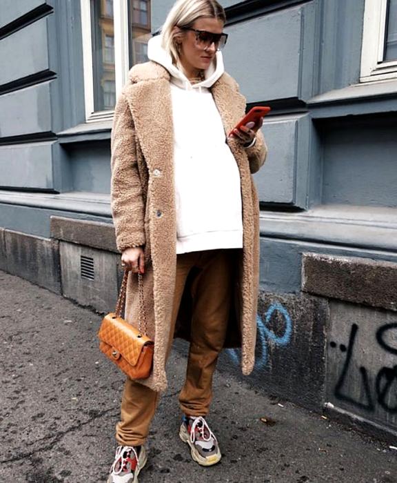 blonde girl with sunglasses, pregnant, wearing a white oversized sweatshirt, brown pants, brown teddy long coat, sneakers and orange handbag